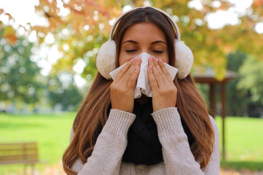 Young woman sneezing and blowing nose into tissue outdoors.
