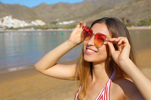 Happy playful girl with sunglasses on the beach