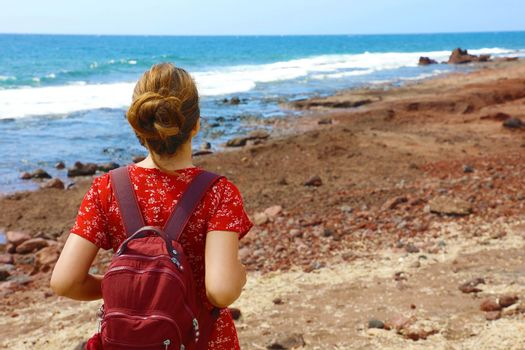 Travel holiday adventure in Tenerife. Back view beautiful young woman breathing and enjoying Tenerife coast. Copy space.