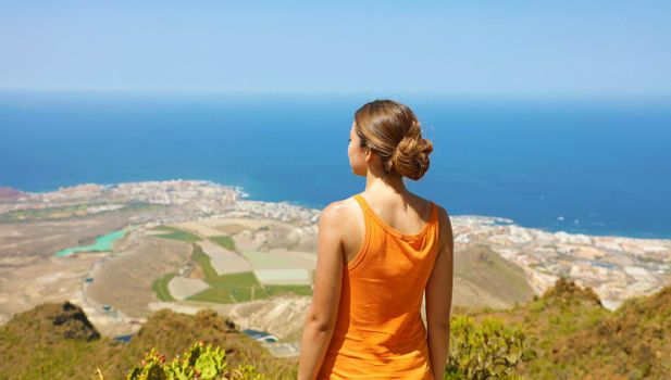 Sporty girl on top view enjoying and breathing in Tenerife Island. Panoramic view from the back.