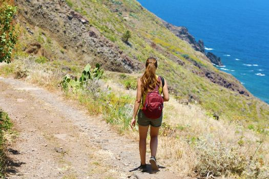 Traveler hiker woman walking along the pathway on Tenerife mountains. Natural tourism backpacker trekking adventure concept.