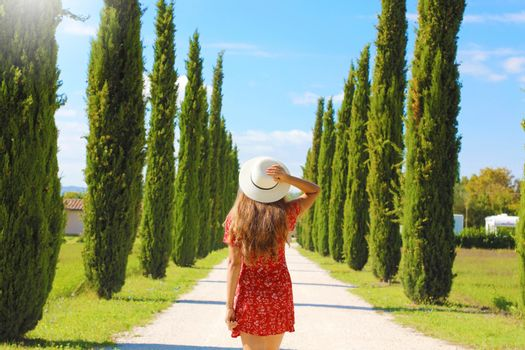 Young woman in Tuscan landscape with cypress trees. Travels in Italy.