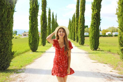 Portrait of beautiful girl in Umbria. Young fashion woman walking in cypresses lane on sunny day. Travels in Italy.