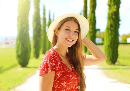 Close up of beautiful girl in Tuscany. Young fashion woman walking in cypresses lane on sunny day. Travels in Italy.