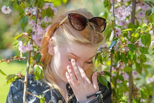 Girl covering her face is posing outdoors.