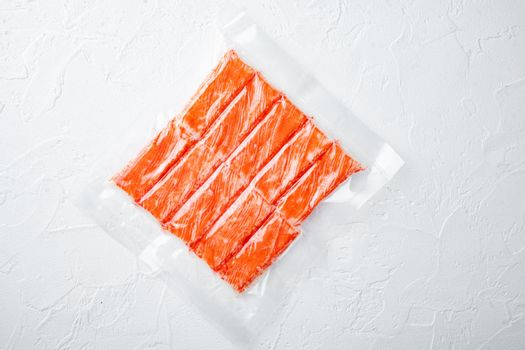 Crab sticks in vacuum pack, on white background, top view flat lay