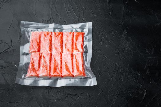 Crab sticks in vacuum pack, on black background, top view flat lay , with copyspace and space for text