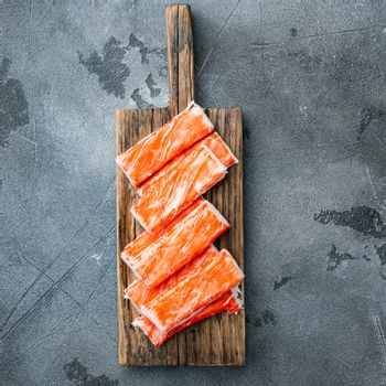 Fresh Crab meat stick surimi with blue swimming crab, on wooden cutting board, on gray background, top view flat lay
