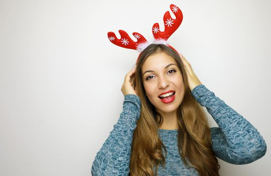 Christmas woman with reindeer horns smiling happy on white background