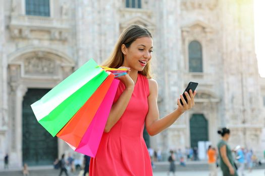 Shopper woman shopping with a smartphone in a commercial square