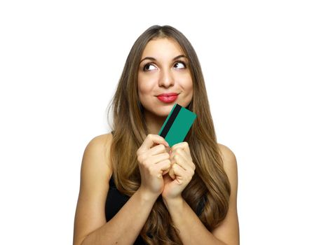Pleased intrigued brunette woman in black dress holding credit card and looking away over white background