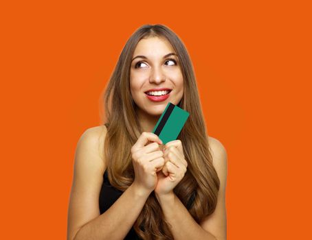 Pleased intrigued brunette woman in dress holding credit card and looking away over orange background