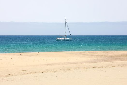 Marine landscape with sailing boat, white sand beach and blue sea. Tranquil scene.