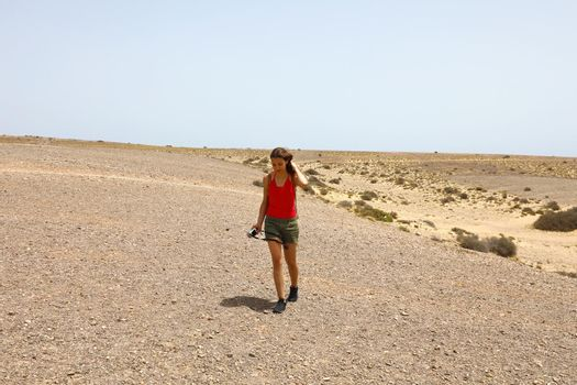 Woman wanderlust having active trip on vacation exploring Lanzarote Island. Hipster girl walking on dry arid surface and enjoying wild nature on Canary Islands.