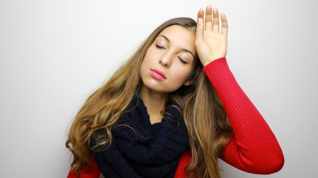 Winter portrait of woman with headache against white background. Copy space.