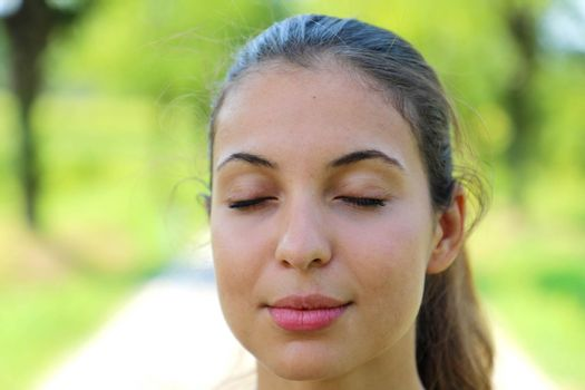 Close-up of young woman with eyes closed meditating