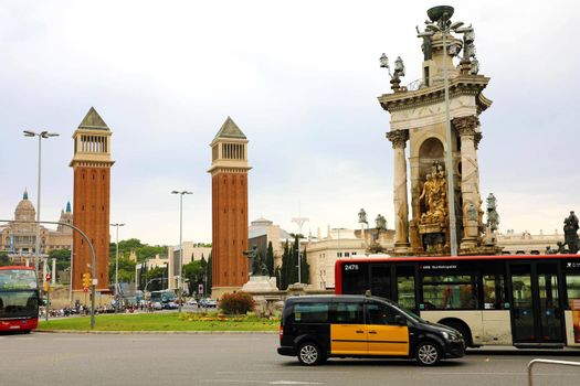 BARCELONA, SPAIN - JULY 13, 2018: Venetian towers in Placa d'Espanya square and the fountain with traffic cars, Catalonia, Spain