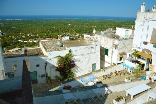 Panoramic view on Ostuni houses with countryside and sea on the background, Italy
