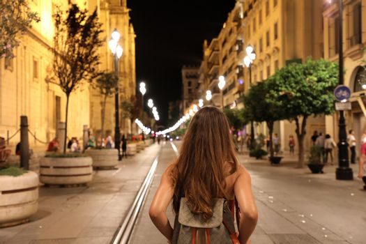 Back view of young tourist woman walking in Seville street in the night, Spain