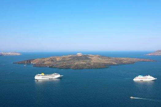 Amazing view from Santorini Island with the caldera of volcano and cruise ships in the sea, Greece