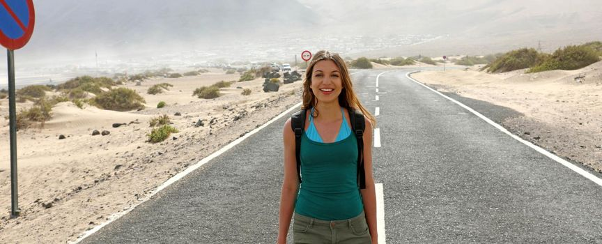 Happy beautiful young woman traveling backpacker adventure on the road panoramic banner cropped