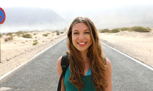 Happy beautiful young woman traveling backpacker adventure on the road