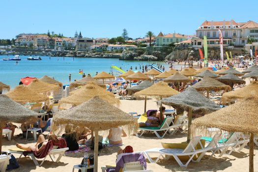 CASCAIS, PORTUGAL - JUNE 25, 2018: tourists and locals sunbathing on the beach in Cascais, Portugal