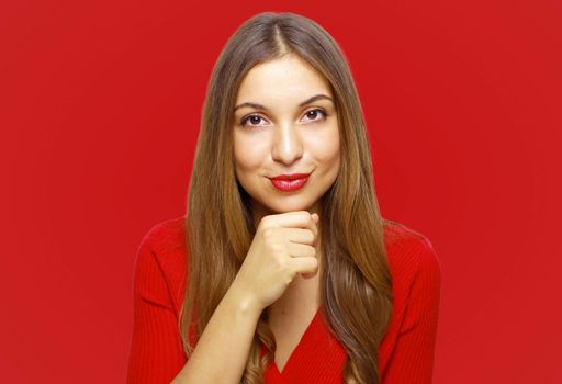 Close up portrait of charming and lovely young woman looks at camera keep her hand on the chin isolated on red background