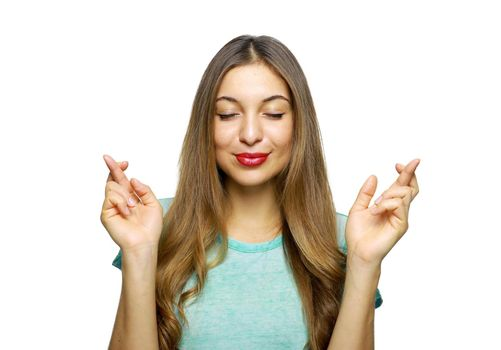 Positive and charming girl wearing azure t-shirt expressing excitement while making with or hoping for something with raised hands and crossed fingers, over white background
