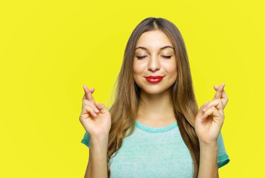 Positive and charming girl wearing azure t-shirt expressing excitement while making with or hoping for something with raised hands and crossed fingers, over yellow background.
