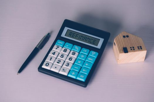 Calculator with text refinance home while expense for loan mortgage, investment and banking, property and cost, real estate and transfer for debt, planning and management of finance, business concept.