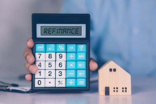 Hands of business man holding calculator for calculate refinance home and expense for loan mortgage, investment and banking, property and finance, real estate and transfer for debt with refinance.