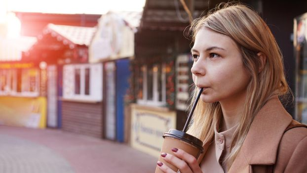 Young blonde with a cup of coffee. Woman at the food court. Glare of the sun