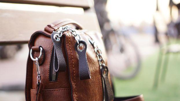 Brown leather bag outside. Blurred summer background