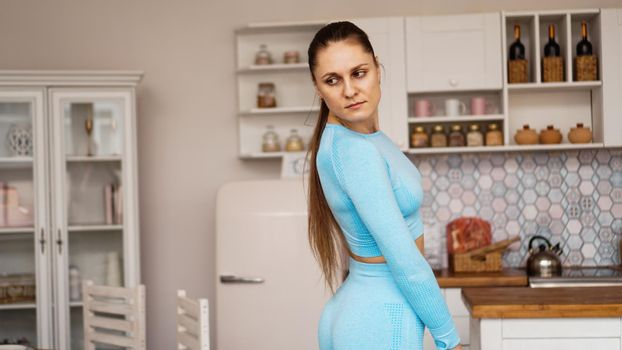 Beautiful woman in sports uniform is preparing for sports training at home