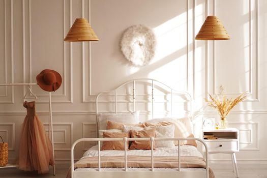 White Scandinavian bedroom in sunshine. Beige accessories