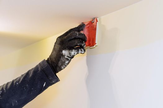 Home renovation on working contractor user in corner paint edger brush painter hands in the painting the wall