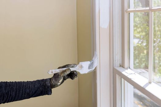 Hand of repairman painting with gloves in the painting window molding trim