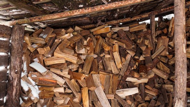 Logging in the village. Chopped logs under a canopy in winter