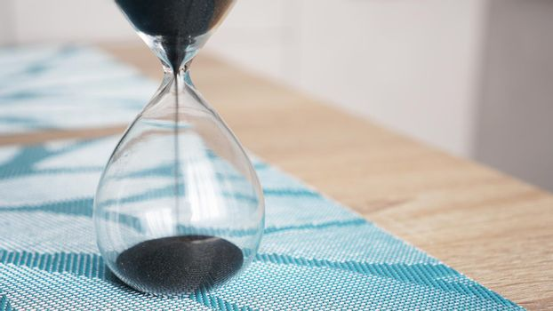 Closeup of hourglass with defocus kitchen on background. Concept of time to cook