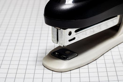 Stapler on the page of a notebook in a cage closeup