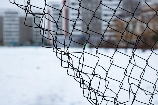 Torn mesh fence on the background of high houses close up