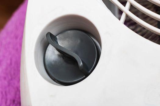 Control knob on a white electronic device close up, macro