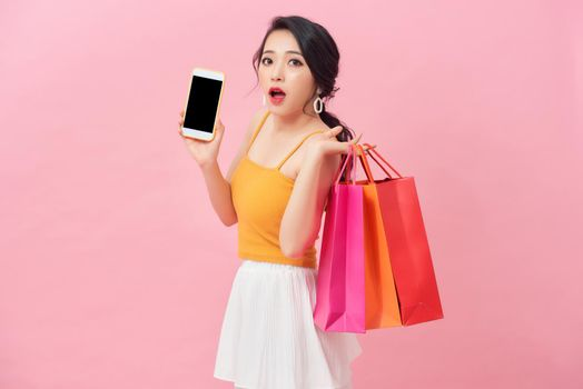 Photo of shocked woman 20s in dress looking at smartphone in hand with surprise while holding shopping bags isolated over pink background
