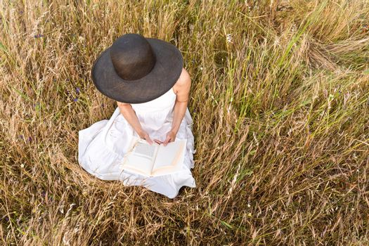 Romantic dreamy top view scene of unrecognizable woman sitting in a field of wheat and tall yellow grass wearing a dark wide-brimmed hat holding a book. Boho girl reading preferred romance story tale