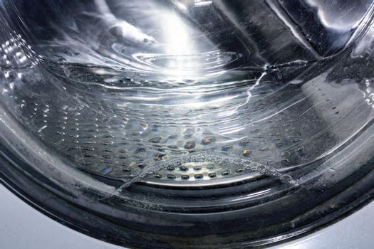 Water in the washing machine drum close up, background for text
