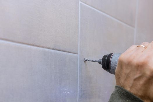Carpenter work drilling hole in bathroom wall for installing bathroom accessories
