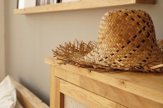 Straw hat on the shelf in room in a Scandinavian style