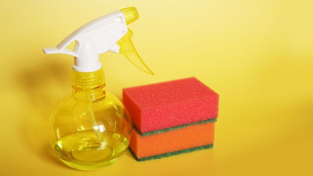Cleaning products on yellow background including spay cleaner and a sponges