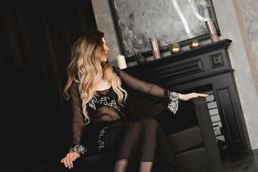 Sexy woman in black peignoir near fireplace